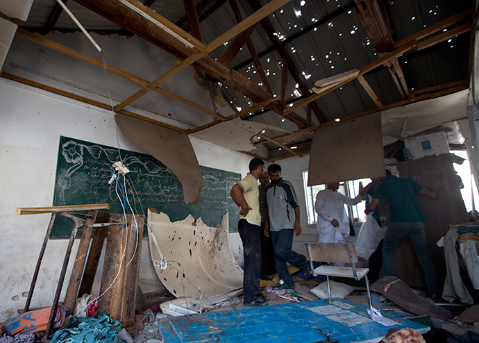 Palestinian men inspect the damage at a UN school at the Jabalia refugee camp in the northern Gaza Strip after the area was hit by Israeli shelling on July 30, 2014 (AFP Photo / Mahmud Hams)