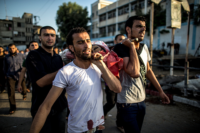 Palestinian mourners carry a body as they walk during a funeral procession past a UN school that was hit by Israeli shelling in the Jabalia refugee camp on July 30, 2014 (AFP Photo / Marco Longari)
