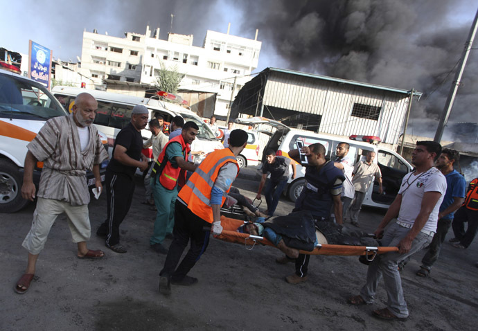 Palestinians carry the body of a local Palestinian journalist, whom medics said was killed by Israeli shelling near a market in Shejaia, as smoke rises in the east of Gaza City July 30, 2014. (Reuters/Ashraf Amrah)