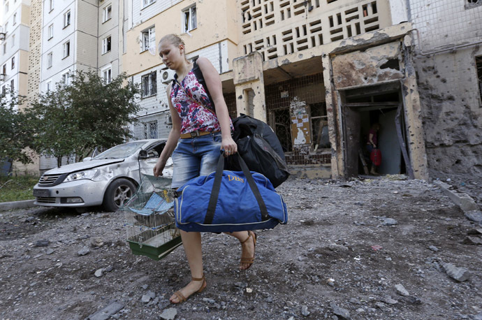 A woman walks out of a damaged multi-storey block of flats carrying her belongings following what locals say was recent shelling by Ukrainian forces in central Donetsk, July 29, 2014. (Reuters/Sergei Karpukhin)