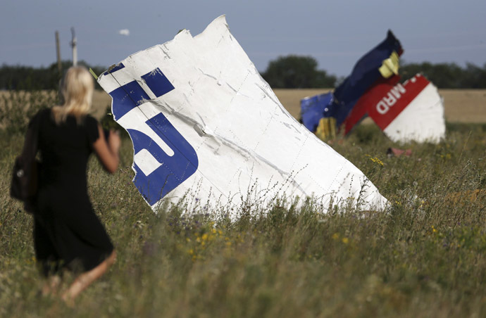 A woman walks past wreckage at the crash site of Malaysia Airlines Flight MH17 near the village of Hrabove (Grabovo), Donetsk region July 26, 2014. (Reuters/Sergei Karpukhin)