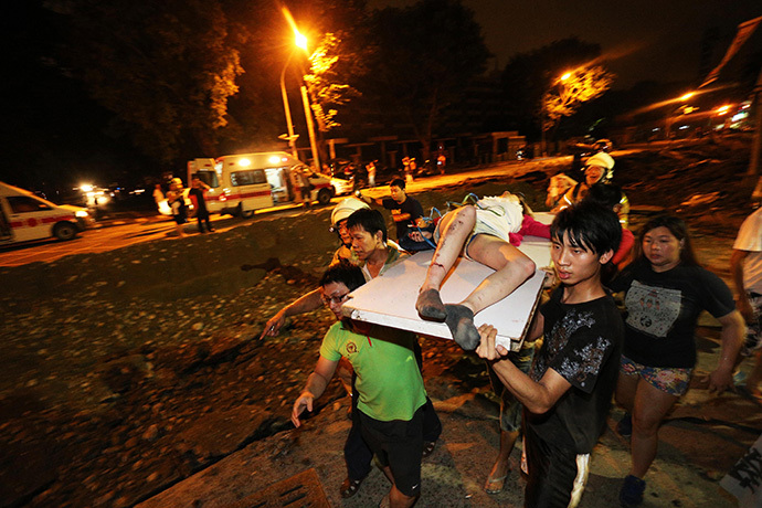 Residents carry a wounded person following a blast in the city of Kaohsiung in southern Taiwan early on August 1, 2014 (AFP Photo / Stringer)