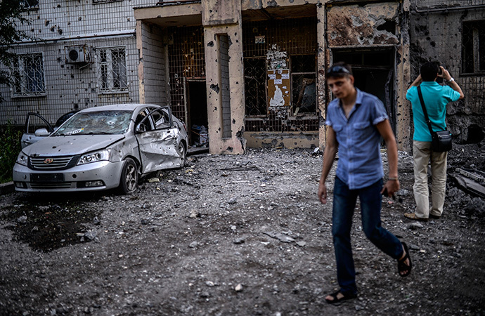 People look at a damaged area after shelling in Donetsk on July 29, 2014. (AFP Photo / Bulent Kilic)
