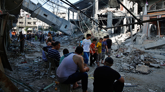 Palestinians gather near the minaret of a mosque that police said was destroyed by an Israeli Air strike in Gaza City July 30, 2014. (Reuters / Finbarr O'Reilly)