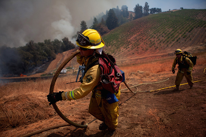 "Marin County firefighters haul a hose on a fire line while battling the fast-moving wildfire called ""Sand Fire,"" near Plymouth, California July 26, 2014. (Reuters / Max Whittaker)"
