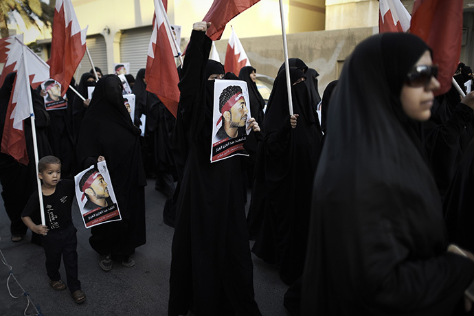 Bahraini women hold up posters bearing the portrait of Abdul Aziz al-Abbar during a protest condemning his death, on July 9, 2014 in the village of Sanabis, west of the capital Manama. (AFP Photo / Mohammed Al-Shaikh)