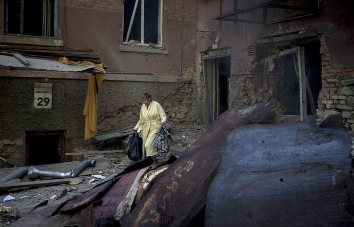 A woman is seen outside a residential building destroyed in an artillery attack by the Ukrainian army on Lugansk.(RIA Novosti / Valeriy Melnikov)