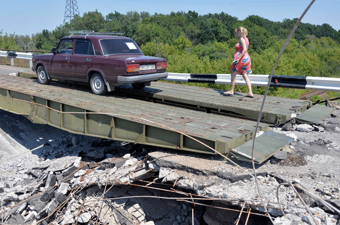 People cross a damaged bridge with their car on August 1, 2014 near the village of Debaltseve, in the Donetsk region, eastern Ukraine. (AFP Photo / Genya Savilov)