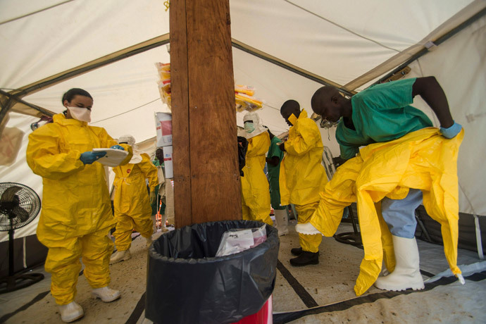 Medical staff working with Medecins sans Frontieres (MSF) put on their protective gear before entering an isolation area at the MSF Ebola treatment centre in Kailahun July 20, 2014.(Reuters / Tommy Trenchard)