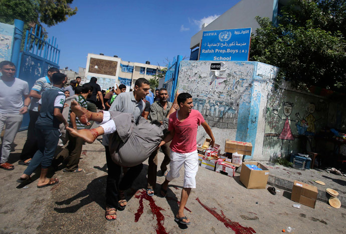 Palestinians carry a wounded man following what witnesses said was an Israeli air strike at a United Nations-run school, where displaced Palestinians take refuge, in Rafah in the southern Gaza Strip August 3, 2014.(Reuters / Ibraheem Abu Mustafa)