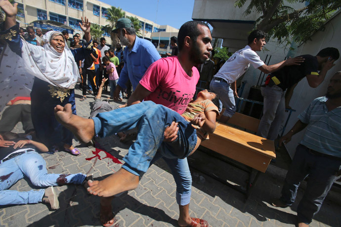 A Palestinian carries a wounded boy following what witnesses said was an Israeli air strike at a United Nations-run school, where displaced Palestinians take refuge, in Rafah in the southern Gaza Strip August 3, 2014.(Reuters / Ibraheem Abu Mustafa)