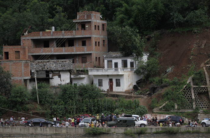 Residents gather near damaged houses following an earthquake in an area of Ludian county in Zhaotong in southwest China's Yunnan province on August 3, 2014. (AFP Photo / China Out )