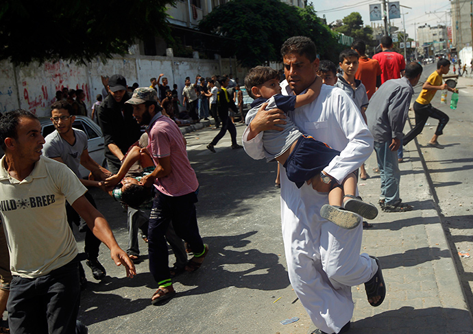 Palestinians carry injured people following an Israeli military strike on a UN school in Rafah, in the southern Gaza Strip on August 3, 2014 (AFP Photo / Said Khatib)