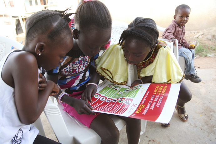 Girls look at a poster, distributed by UNICEF, bearing information on and illustrations of best practices that help prevent the spread of Ebola virus disease (EVD), in the city of Voinjama, in Lofa County, Liberia in this April 2014 UNICEF handout photo. (Reuters/UNICEF)