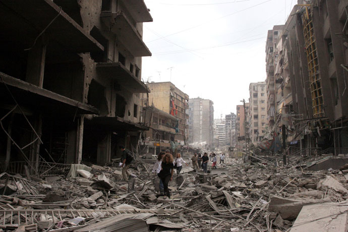Journalist inspect the damaged buildings after Israeli air raids in southern Beirut July 20 2006. (Reuters)