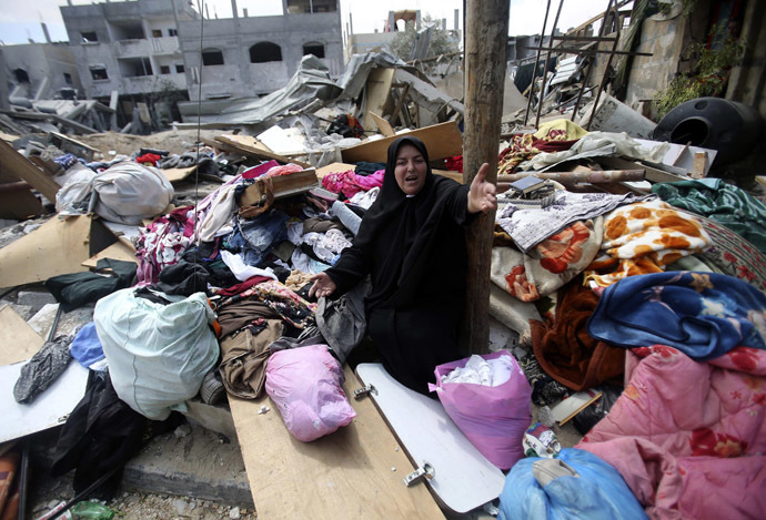 A Palestinian woman reacts as she collects her belongings from her house which witnesses said was destroyed in an Israeli air strike, in Rafah in the southern Gaza Strip August 4, 2014. (Reuters/Ibraheem Abu Mustafa)