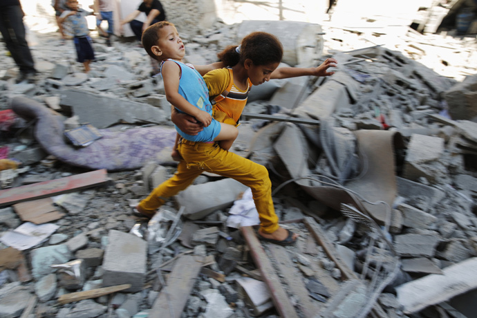 A Palestinian girl carries a child across rubble from a building that police said was destroyed by an Israeli air strike, in the Burij refugee camp in the central Gaza Strip (Reuters / Finbarr O'Reilly)