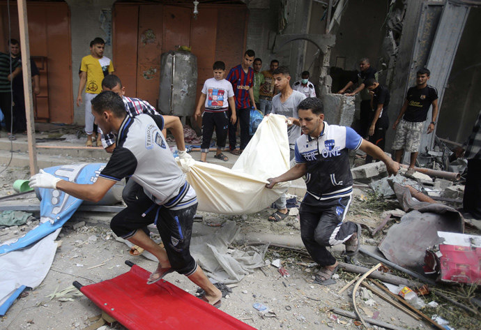 Palestinians carry the dead body of a woman after removing it from under the rubble of a house which witnesses said was destroyed in an Israeli air strike, in Rafah in the southern Gaza Strip August 4, 2014. (Reuters / Ibraheem Abu Mustafa)