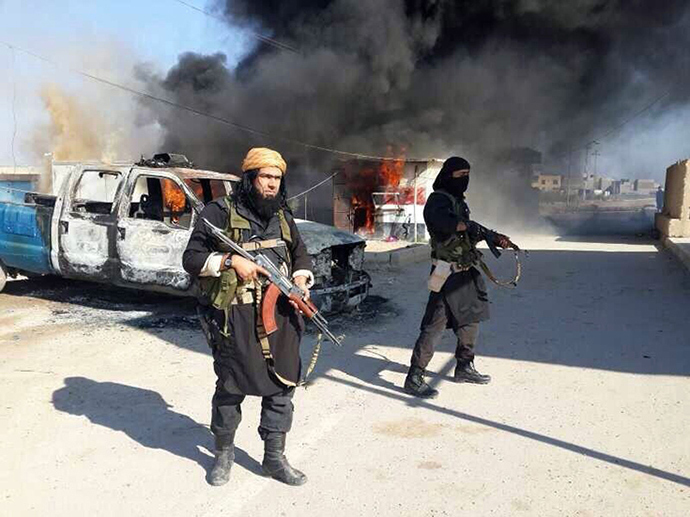 An image uploaded to an Islamic website on January 8, 2014, allegedly shows Shakir Wahib (L), Abu Wahib, a leader of the Islamic State of Iraq and the Levant (ISIS) standing next to burning cars (AFP Photo)
