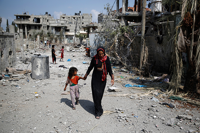 A Palestinian woman leads a girl past destroyed buildings after returning to Beit Hanoun town, which witnesses said was heavily hit by Israeli shelling and air strikes during the Israeli offensive, in the northern Gaza Strip August 5, 2014 (Reuters / Finbarr O'Reilly)