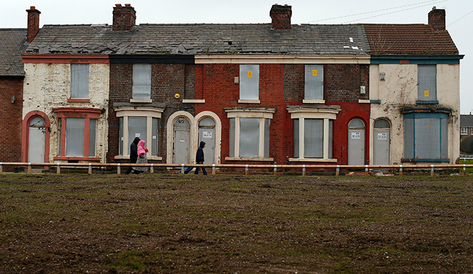 People walk past a row of boarded up terraced houses in the Kensington area of Liverpool, northern England (Reuters / Phil Noble)