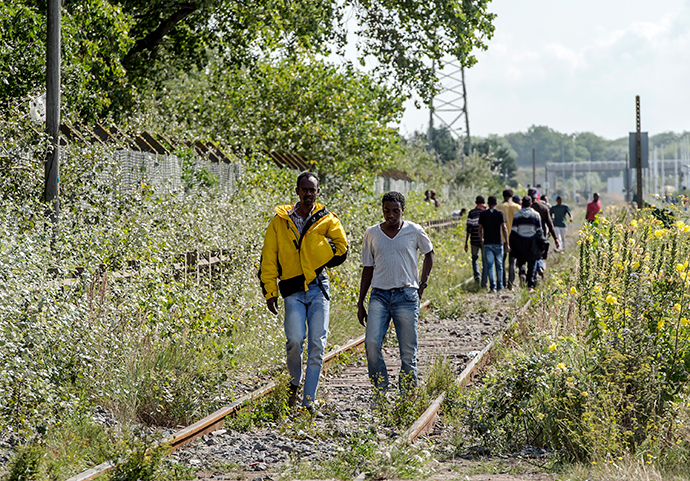 Migrants walk on a railway in Calais, northern France, on August 5, 2014 (AFP Photo / Pilippe Huguen)