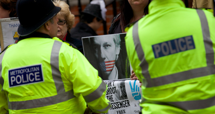 Police stand guard in front of supporters of WikiLeaks founder Julian Assange who are standing with banners outside the Ecuadorian Embassy in London on June 19, 2014 (AFP Photo / Andrew Cowie)