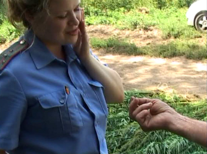 Screenshot from Russian police video - A police officer is helped after she is stung by a bee when helping to clear hundreds of cannabis plants not far from Kostroma, which is around 350 kilometers north east of Moscow. August 5, 2014