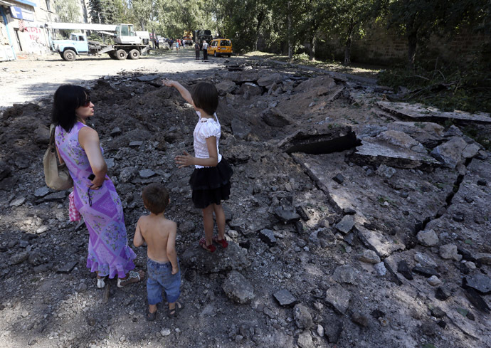 Local residents stand in a crater following what locals say was recent airstrike by Ukrainian forces in Donetsk, August 6, 2014. (Reuters/Sergei Karpukhin)