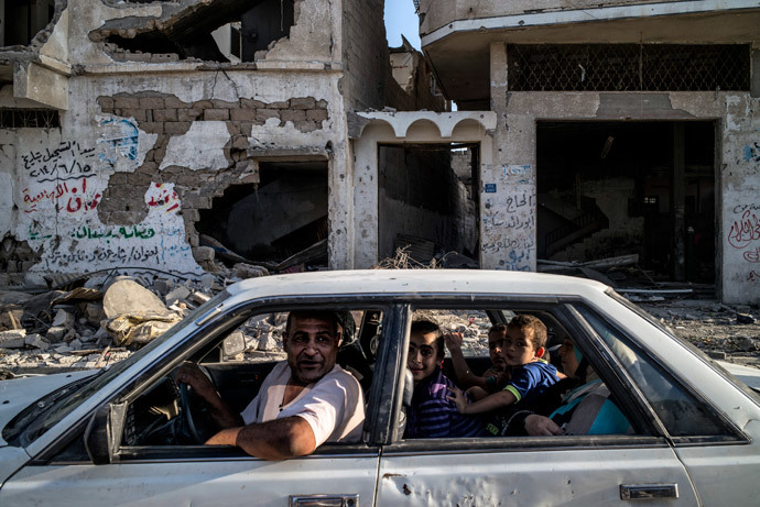 A Palestinian family drves past a destroyed building in the devastated neighbourhood of Shejaiya in Gaza City on August 6, 2014.(AFP Photo / Marco Longari)