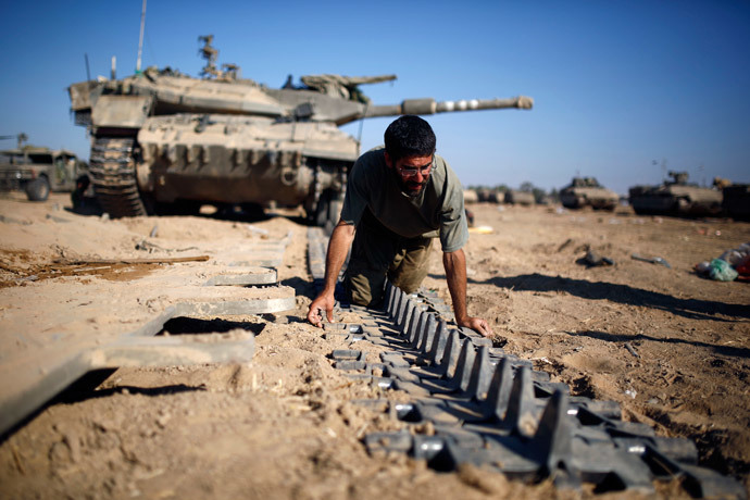 An Israeli reserve soldier checks a tank track near the border with Gaza August 6, 2014.(Reuters / Amir Cohen)
