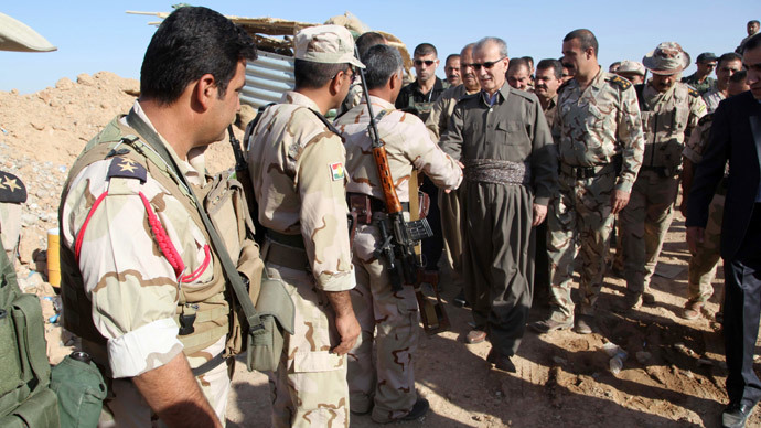 Kirkuk provincial Governor Najm al-Din Karim (C) shakes hands with Kurdish peshmerga forces in the district of Daquq.(AFP Photo / Marwan Ibrahim)