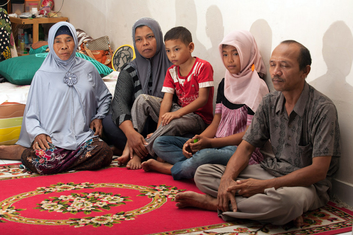 Missing Indonesian tsunami victim Raudhatul Jannah (2nd R), aged 14, sits with mother Jamaliah (2nd L), holding youngest son Jumadi Rangkuti (C) and father Septi Rangkuti (extreme R), joined by Syarwani (L), the foster mother who has raised Jannah in the city of Meulaboh, (AFP Photo / Chaideer Mahyuddin)