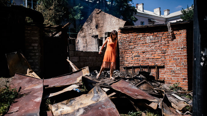 A woman walks through wreckage after shelling in Donetsk on August 9, 2014.(AFP Photo / Dimitar Dilkoff)