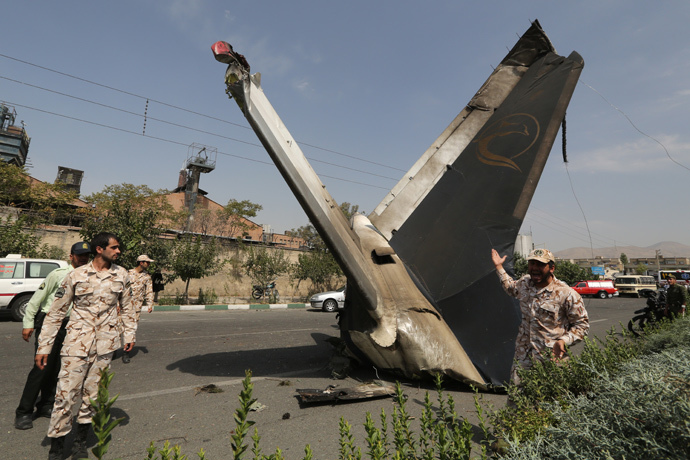 A member of the Iranian Revolutionary Guards reacts as he stands next to the remains of a plane that crashed near Tehran's Mehrabad airport on August 10, 2014. (AFP Photo / Atta Kenare)