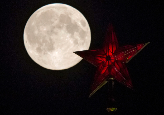 The supermoon rises over the stars of Moscow's Kremlin towers in Moscow August 10, 2014 (Reuters / Maxim Shemetov)