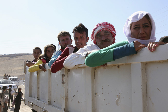 Displaced people from the minority Yazidi sect, fleeing the violence in the Iraqi town of Sinjar, re-enter Iraq from Syria at the Iraqi-Syrian border crossing in Fishkhabour, Dohuk Province, August 10, 2014. (Reuters/Ari Jalal)