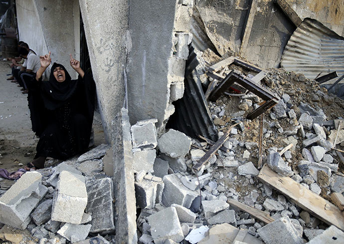 A Palestinian woman reacts next to the rubble of her relatives' house, which police said was destroyed in an Israeli air strike, in the southern Gaza Strip July 21, 2014. (Reuters / Ibraheem Abu Mustafa)