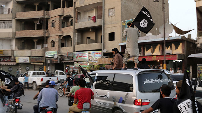 Members loyal to the Islamic State in Iraq and the Levant (ISIL) wave ISIL flags as they drive around Raqqa June 29, 2014. (Reuters)