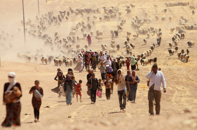 Displaced people from the minority Yazidi sect, fleeing violence from forces loyal to the Islamic State in Sinjar town, walk towards the Syrian border, on the outskirts of Sinjar mountain, near the Syrian border town of Elierbeh of Al-Hasakah Governorate August 10, 2014. (Reuters / Rodi Said)
