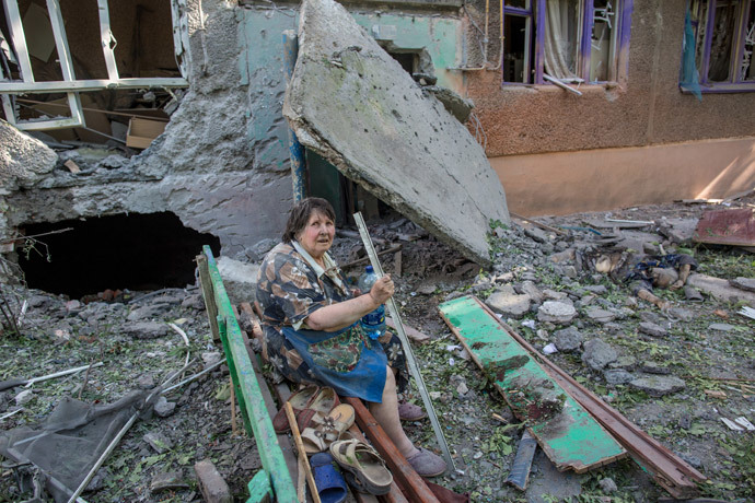 Resident of a building destroyed by an artillery bombardment of Slavyansk by Ukrainian servicemen and her neighbor who was killed when she was sitting on a bench in near the doorway. (RIA Novosti / Andrey Stenin)