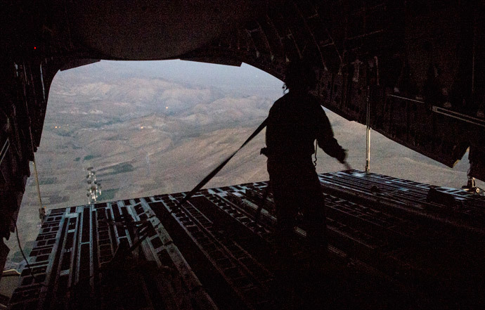 Tech. Sgt. Lynn Morelly, 816th Expeditionary Airlift Squadron, C-17 Globemaster III loadmaster, watches bundles of halal meals parachute to the ground during a humanitarian airdrop mission over Iraq in this August 9, 2014 photo (Reuters / Vernon Young Jr. / U.S. Air Force / Handout)