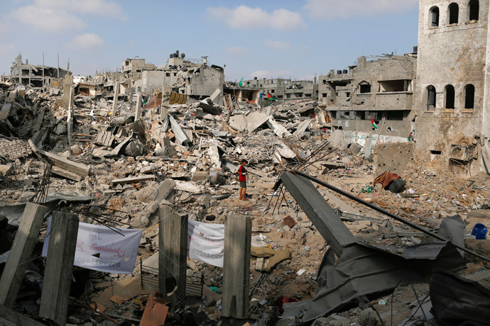 A boy stands amid the ruins of buildings that witnesses say were destroyed by Israeli air strikes in the Shejaia neighbourhood in Gaza City August 12, 2014. (Reuters / Siegfried Modola)