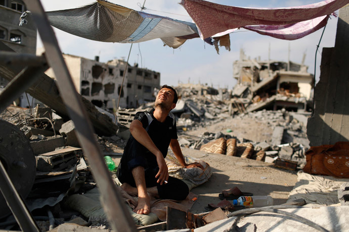 A man looks up as he sits in a tent amid the ruins of his home that he says was destroyed by Israeli air strikes in the Shejaia neighbourhood in Gaza City August 12, 2014. (Reuters / Siegfried Modola)