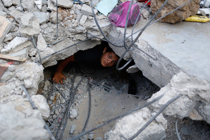 A boy looks at the camera as he tries to salvage some belongings from the ruins of his family's apartment that witnesses say was destroyed by Israeli air strikes in the Shejaia neighbourhood in Gaza City August 12, 2014. (Reuters / Siegfried Modola)