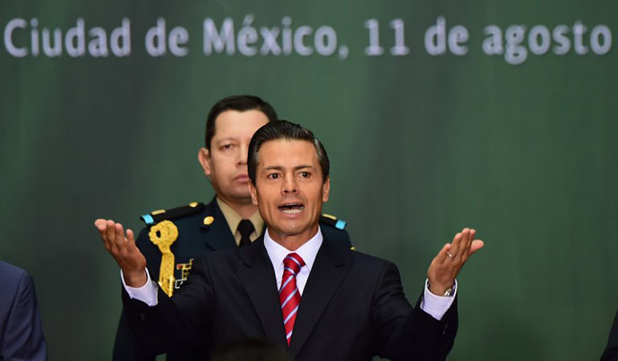 Mexican president Enrique Pena Nieto delivers a speech before signing the new law of energy, in Mexico City, on August 11, 2014. (AFP Photo / Ronaldo Schemidt)