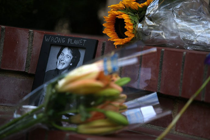 Flowers and pictures that are part of a growing memorial sit on the steps in front of the home where actor and comedian Robin Williams filmed the movie Mrs. Doubtfire on August 12, 2014 in San Francisco, California. (AFP Photo / Getty Images Justin Sullivan)