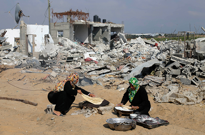 Palestinian women bake bread in front of the remains of their house, which witnesses said was destroyed in the Israeli offensive, during a 72-hour truce in Khan Younis the southern Gaza Strip August 13, 2014 (Reuters / Ibraheem Abu Mustafa)