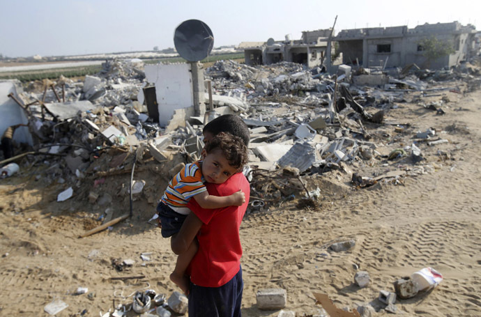 A Palestinian boy carries his brother next to the remains of their house, which witnesses said was destroyed in the Israeli offensive, during a 72-hour truce in Khan Younis the southern Gaza Strip August 13, 2014. (Reuters/braheem Abu Mustafa)