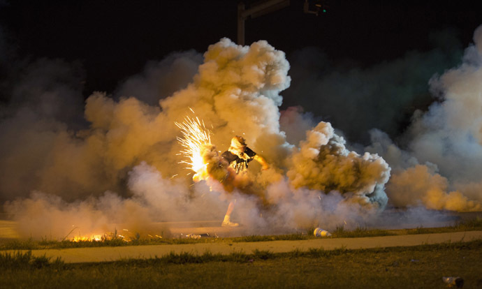 A protester throws back a smoke bomb while clashing with police in Ferguson, Missouri August 13, 2014. (Reuters)